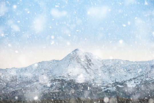 Beautiful Winter sunrise landscape image of Mount Snowdon and other peaks in Snowdonia National Park in heavy snow storm