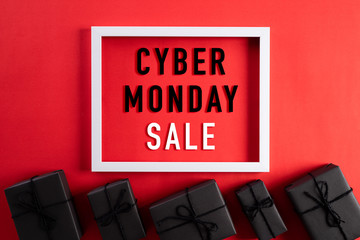 Top view of Cyber Monday Sale text on white picture frame with black gift box and on red background. Shopping online concept and Cyber Monday composition.