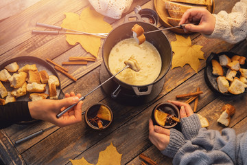 Meeting of friends, girl is cooking Swiss fondue assorted cheeses dinner on fire, hands holding mulled wine background wood board, top view