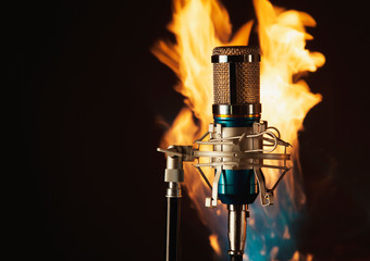 Metal microphone on a fire and dark  background  photo