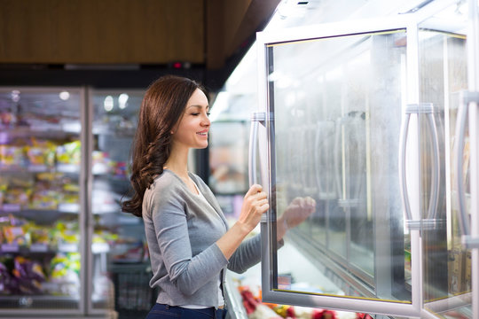 Woman choosing a dairy products at supermarket. Reading product information