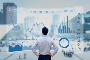 Finance trade manager analysing stock market indicators for best investment strategy, financial data and charts with business buildings in background Wall mural