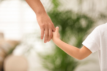 Mother holding hands with her child indoors, closeup. Happy family