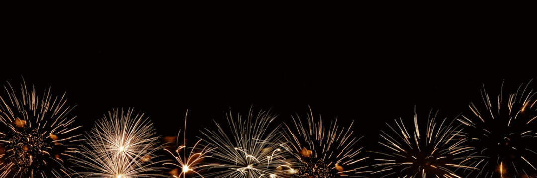 Golden fireworks panoramic background with copyspace, new year and holiday night party web banner