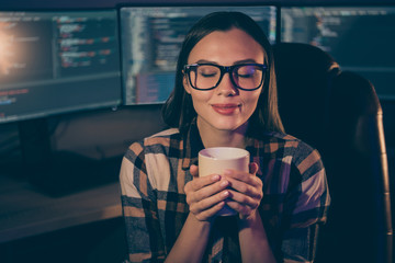Photo of pleased satisfied cheerful joyful girl in spectacles enjoying aroma of freshly brewed coffee on the background of script java monitors