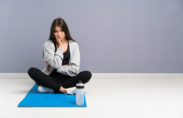 Young sport woman sitting on the floor with mat unhappy and frustrated