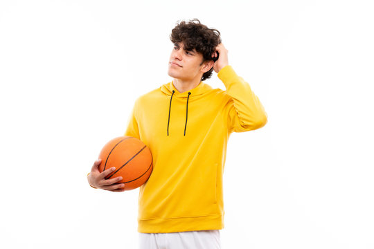 Young basketball player man over isolated white wall having doubts and with confuse face expression