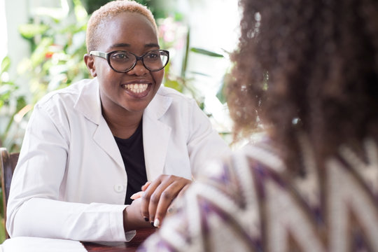 A young African American female doctor with glasses shakes hands with a patient as a sign of trust of a doctor. People of mixed race In the doctors office