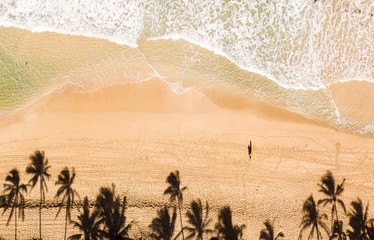 Aerial photo of a surfer on a beach in Hawaii