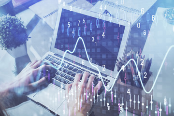 Double exposure of man's hands writing notes with laptop of stock market with forex graph background. Top View. Concept of research and trading.