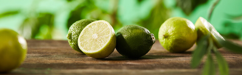 panoramic shot of cut and whole limes on wooden surface
