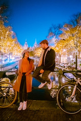 ( little nois in pic during the night ) couple standing on a bridge in Amsterdam at night with christmas lights in the trees alongside the canals in Amsterdam city