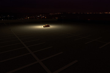 3D rendering of a sinngle car in a parking lot representing the concept of working late Fototapete