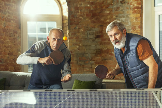 Senior men playing table tennis in workplace, having fun. Friends in casual clothes play ping pong together at sunny day. Concept of leisure activity, sport, friendship, teambuilding, teamwork.