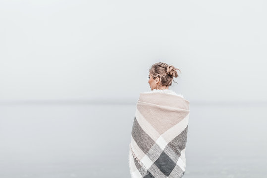 Pretty blonde woman wrapped in warm blanket standing on the cold autumn beach.