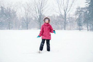 Cute adorable funny Caucasian smiling laughing girl child in warm clothes red pink jacket playing with snow having fun during cold winter snowy day. Kids outdoor seasonal activity.