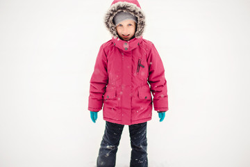 Portrait of cute funny Caucasian smiling girl child in warm clothes red pink jacket playing with snow during cold winter snowy day and looking at camera. Kids outdoor seasonal activity.