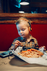 Portrait of cute adorable funny little boy toddler playing digital toy cell phone gadget with ear phones and eating food meal in restaurant. Child using modern kids technology entertainment.