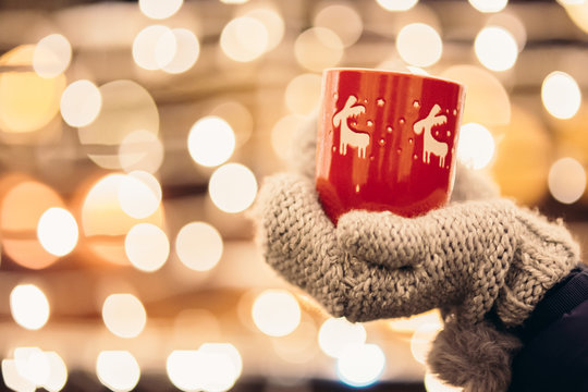 Christmas light and a woman holding in hand a red mug with hot drink