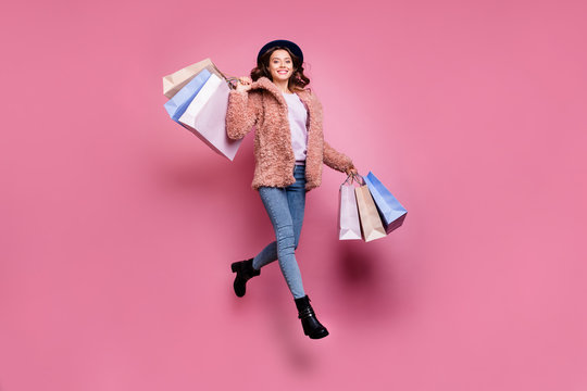 Full length photo of beautiful model millennial lady jumping high enjoy sales carry many packs store wear fluffy jacket retro blue hat jeans isolated pink background
