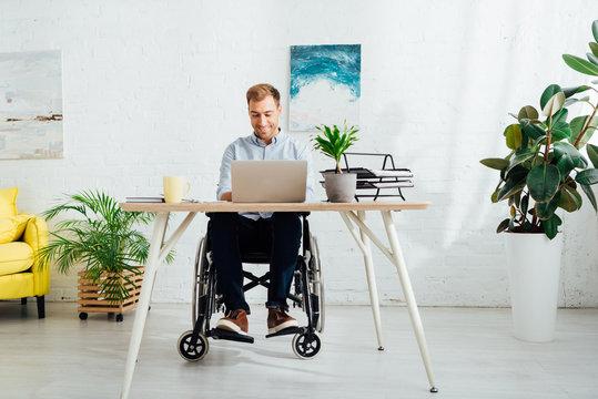 Smiling freelancer in wheelchair using laptop at desk in living room