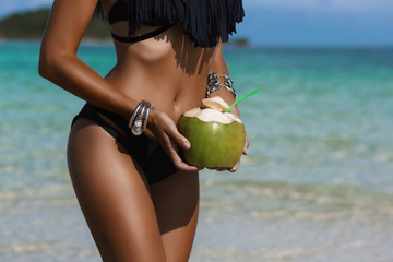 Beautiful tanned sexy lady, a perfect body, holding a fresh coconut, against the background of a tropical island, on the beach, vacation travel, happiness and relaxation