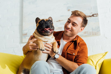 Happy man holding funny french bulldog on sofa in living room