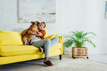 Happy man playing with french bulldog on sofa in living room