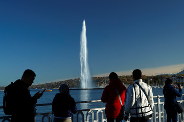 Tourists take pictures in front of the jet d'eau water fountain in Geneva