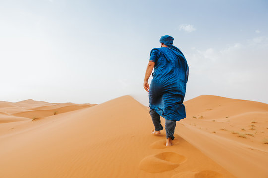 Man with classic berber clothes on walking by the desert dunes alone.