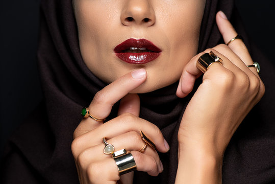 cropped view of beautiful Muslim woman in hijab with makeup in golden rings isolated on black