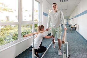 Therapeutin hilft jungem Mann, der nach einem Unfall in der Reha wieder laufen lernt