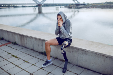 Fotomurales - Fit healthy caucasian handicapped sportsman with artificial leg and hoodie on head sitting on quay and resting.