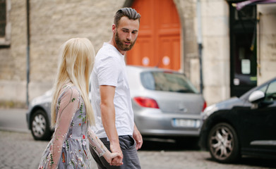 Couple in love hugging and relaxing in Paris/ They are wearing trendy clothes. Man is a hipster with a beard wearing white t-shirt Wall mural