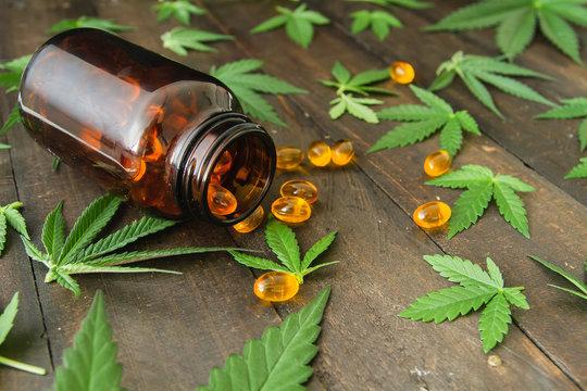 CBD oil capsules and hemp leaves