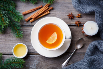 Cup of tea with honey, lemon. Winter hot beverage. Grey wooden background. Top view.