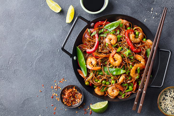 Stir fry noodles with vegetables and shrimps in black iron pan. Slate background. Copy space. Top view.