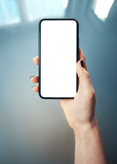 Mockup image of woman's hand holding thin bezels mobile phone with blank screen in glossy and blurry corporate environment - Image