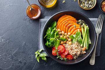 Healthy vegetarian salad. Roasted pumpkin, quinoa, tomatoes, green salad. Buddha bowl. Slate background. Top view.