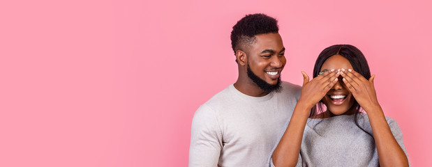 Black guy making surprise for girlfriend over pink background