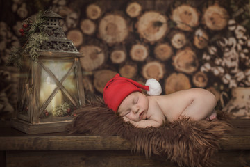 Christmas newborn baby boy girl sleeping in front of a pile of wood logs in a cabin with a red santa claus hat on a rug with a glowing lantern nearby