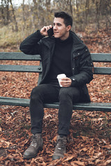 Young Smiling Man Wearing Coat Talking On Cellphone And Drinking Takeaway Coffee In Autumn park .