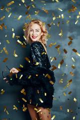 Pretty blonde woman in little black dress dancing on confetti