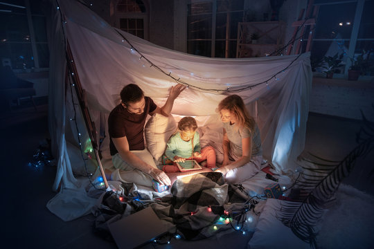Caucasian family sitting in a teepee, having fun and playing with the flashlight in dark room with toys and pillows. Look happy. Home comfort, family, love, Christmas holidays, storytelling time.