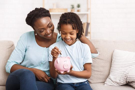 Little african american girl saving money to piggy bank