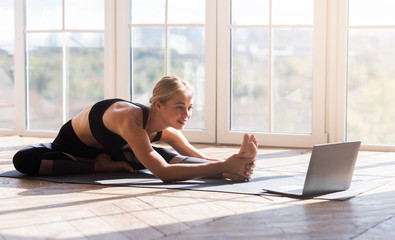 Foto op Plexiglas School de yoga Flexible girl doing yoga at home, looking at laptop screen