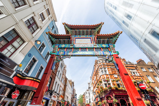 London, UK - June 24, 2018: Wide, low angle view looking up of Chinatown China town gate street road with nobody, downtown city, Chinese sign, red colorful buildings