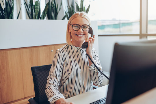 Smiling businesswoman sitting at her desk talking on a telephone