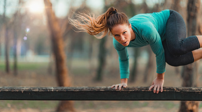Woman Jumping Over the Wooden Huddles