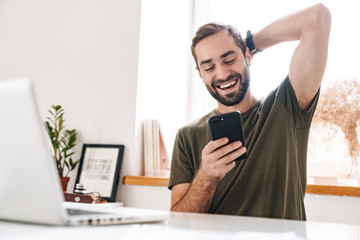 Image of handsome laughing man typing on laptop and using cellphone